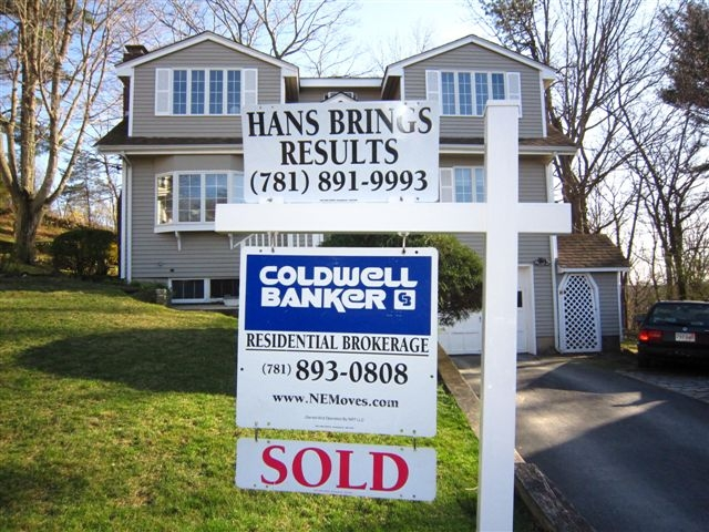 hans brings sold sign in front of house