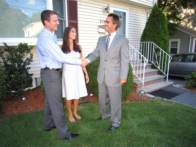 realtor shaking hands with couple
